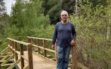 Paul Bisson stands with the newly finished horseback rider bridge over Cranberry Brook in SVT's Memorial Forest.